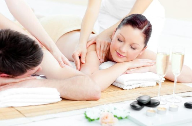 a woman and man enjoying a beach front couples massage